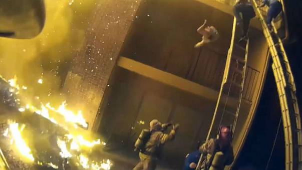 Firefighter catches child dropped from second floor of burning building