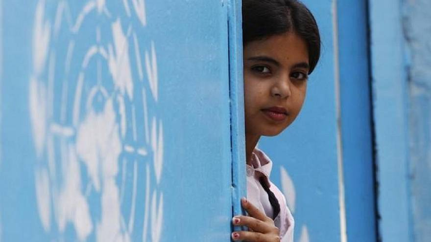 طفلة وإلى جنبها شعار وكالة أنروا