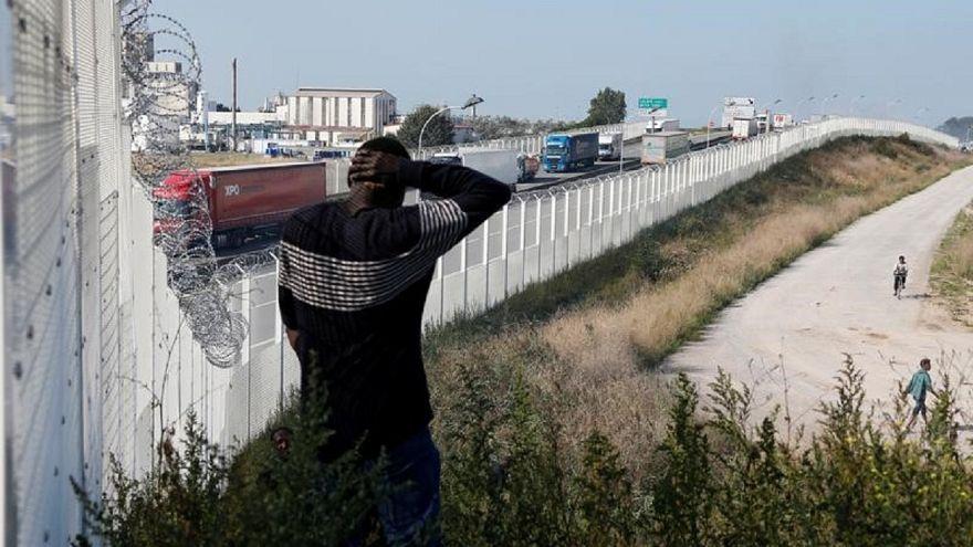 مهاجر يسير بمحاذاة سياج في كاليه يحول دون عبور المهاجرين إلى بريطانيا
