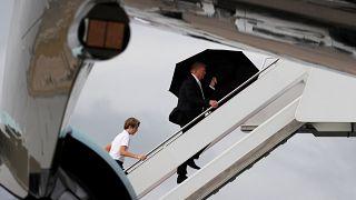 Trump unter dem Schirm, Melania und Sohn im Regen