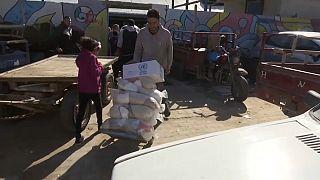 Ein Palästinenser befördert UN-Hilfslieferungen auf einer Sackkarre.