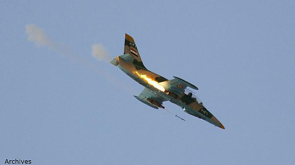 A Syrian Air Force fighter plane fires a rocket during an air strike in the