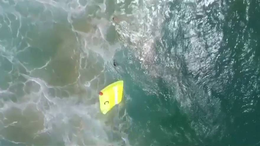 Lifeguard drone dropping float into water close to two swimmers in trouble