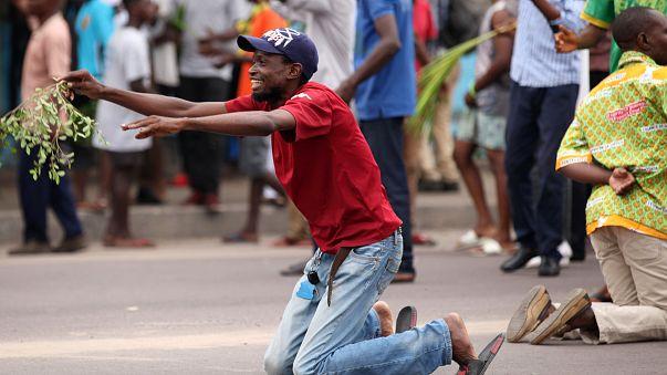 Un manifestant anti-Kabila à genoux devant la police à Kinshasa.