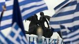 A statue of Alexander the Great is seen through waving Greek national flags