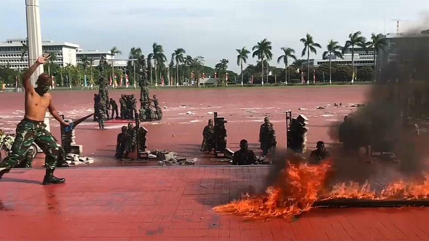 شاهد: جنود إندونيسيون يشربون دماء الأفاعي ويمشون حفاة على النار