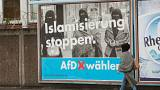 A woman with a headscarf walks past an election campaign poster of the AfD