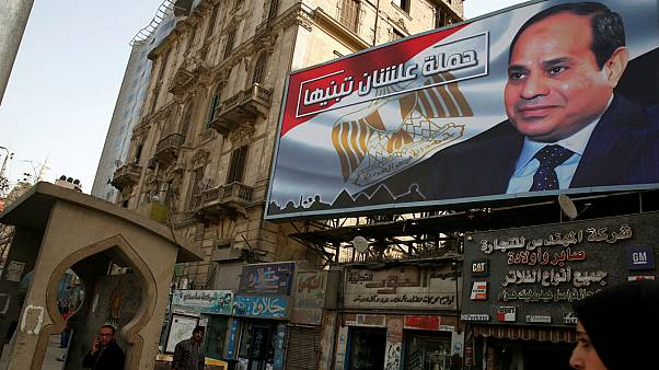 People walk by a poster of Egypt's President Abdel Fattah al-Sisi in Cairo