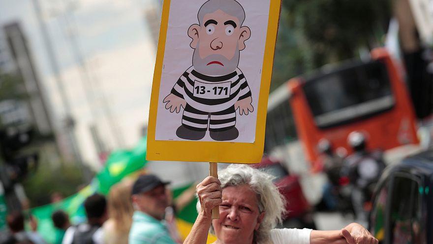 Manifestante llevando una pancarte de Lula vestido de prisionero