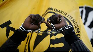 A migrant living in Greece protests reports of migrant slavery in Libya