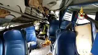 Tűzoltók dolgoznak az egyik összeroncsolódott vasúti kocsiban