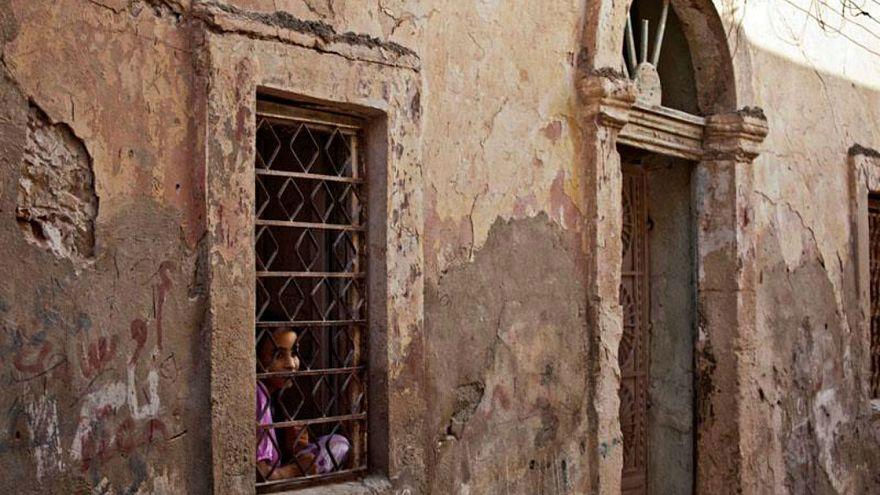 فتاة  تطل من نافذة منزلها في بنغازي، ليبيا.