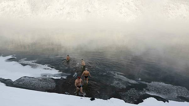 Members of the Dolphin winter swimming club enter the icy water