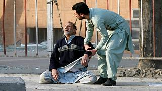 Injured man receives medical assistance after a blast in Kabul