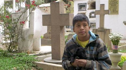 Benjamin Obando, 11, prays and sings at a cemetery in Cochabamba.