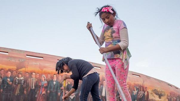 An 8-year-old and her friend sweep the pavement in La Paz.