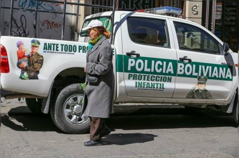 A woman walks past a police truck marked