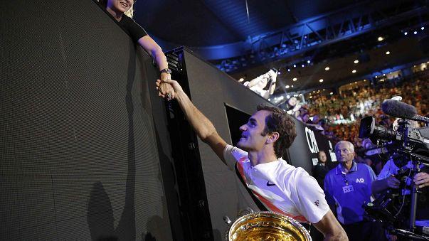 Roger Federer con su trofeo estrecha la mano de su mujer Mirka