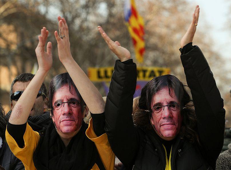 كتالونيا متظاهرين يلبسون أقنعة تحمل صورة بودجمون