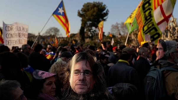 A demonstrator wears a mask depicting ouster separatist leader Puigdemont