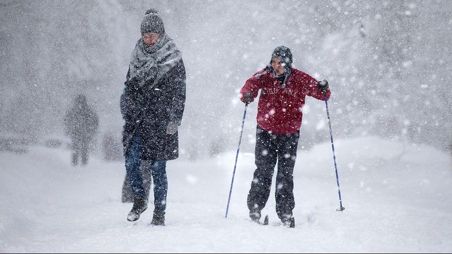 Síléceken és gyalogosan közlekedők a sűrű hóesésben egy moszkvai parkban