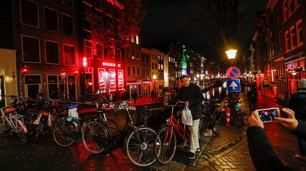 A tourist poses for a photo near a canal in the red district of Amsterdam,