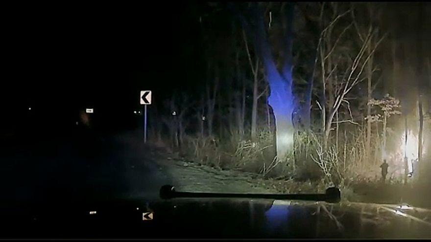 Rendőr szalad a lángoló autó felé