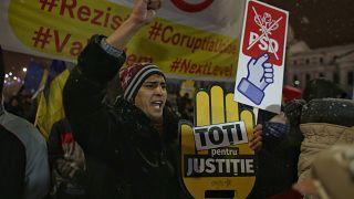 Ein Mann streckt seine Faust in die Luft während einer Demo in Bukarest.
