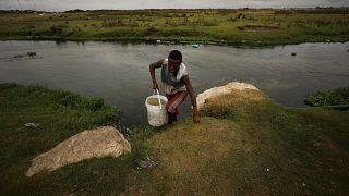 Ein Mann holt Wasser aus einem verschmutzten Fluss.