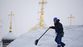 A worker removes snow from the roof of a building in Moscow