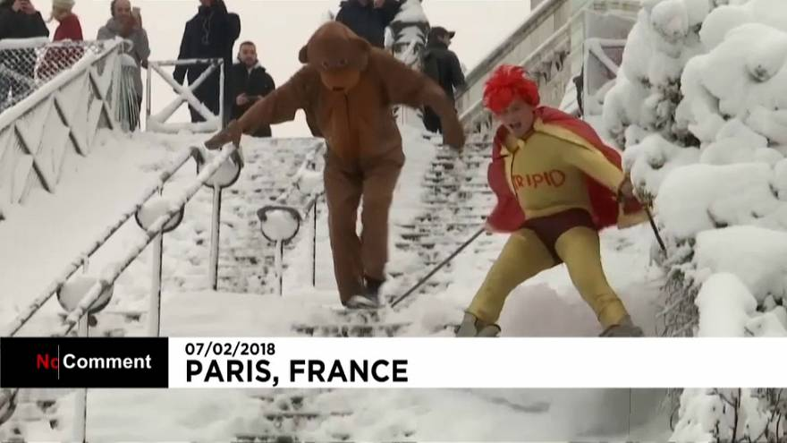 A super hero and his sidekick snow down the slopes of Sacre Coeur
