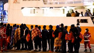 Migrants disembark from the MV Aquarius, a search and rescue ship run in pa