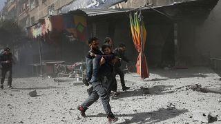 Ein Mann rennt mit einem Mädchen auf dem Arm nach einem Luftangriff.
