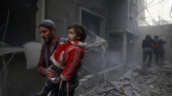 Un hombre con un niño en brazos en la localidad de Duma, en Guta Oriental