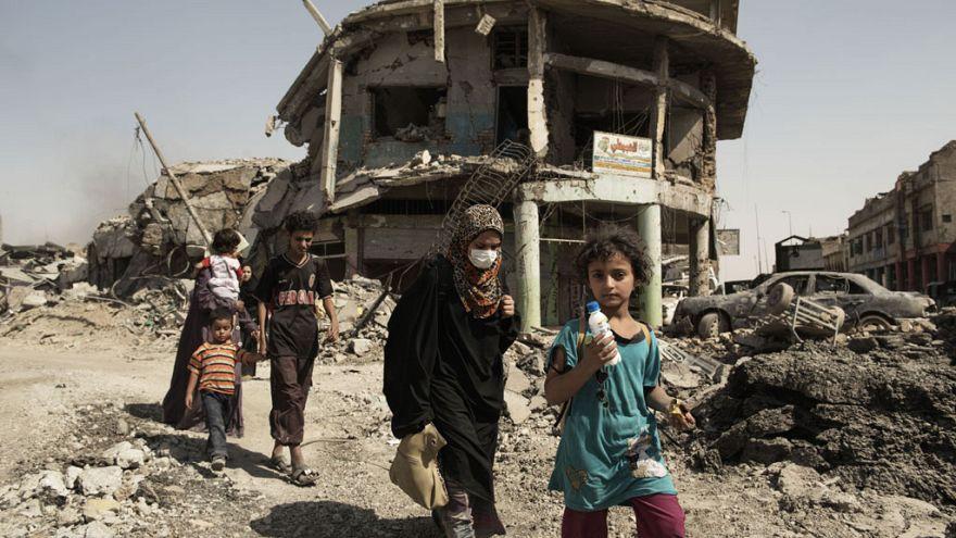 نساء وأطفال يتنقلون عبر حطام المباني والمركبات التي دمرت أثناء القتال