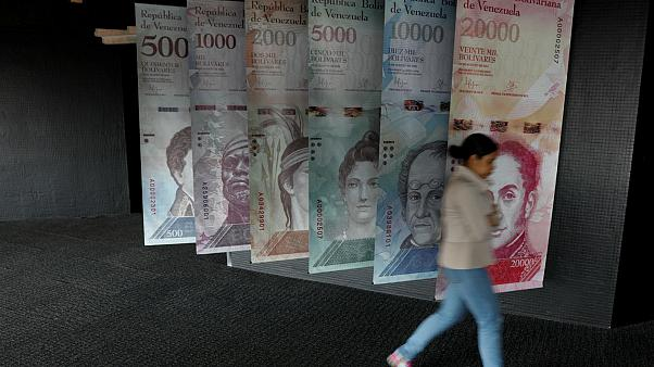 A woman walks by banners of Venezuelan bolivar