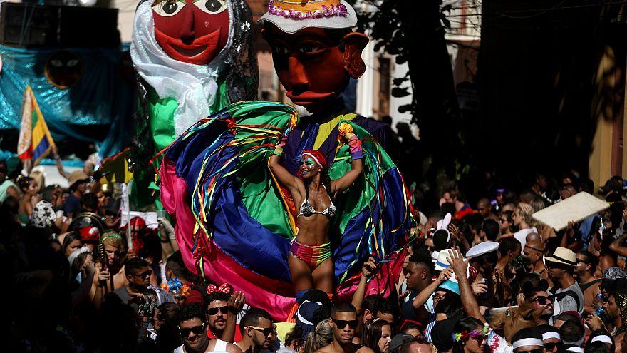 Eine bunt gekleidete Frau tanzt beim Karneval in Rio de Janeiro.