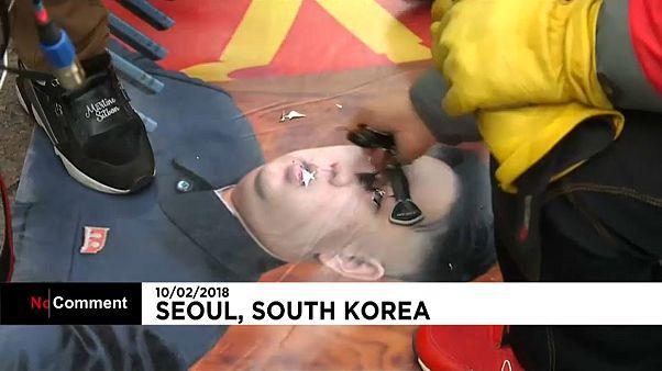 Ein Demonstrant ritzt mit einem Schlüssel in ein Bild Kim Yong Uns.
