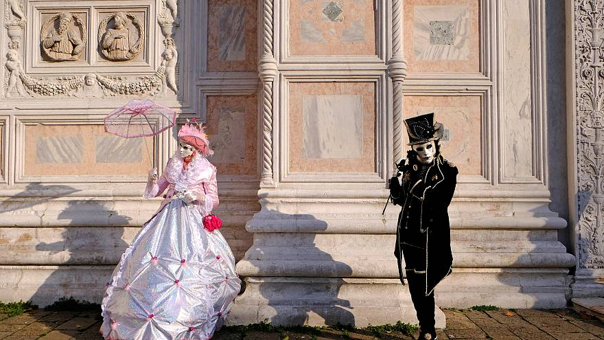 Masked revellers pose during the Venice Carnival in Venice, Italy