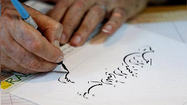 خطاط يكتب آية من القرآن