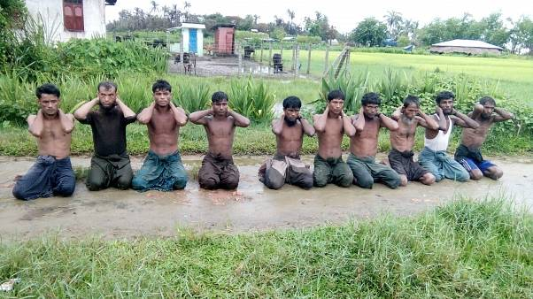 Ten Rohingya Muslim men with their hands bound kneel in Inn Din village