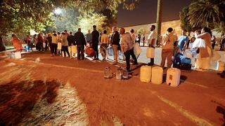 People queue to collect water from a spring in Cape Town