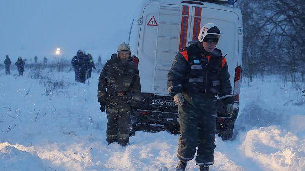 عمال في خدمات الطوارئ في موقع سقوط طائرة روسية قرب موسكو