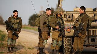 جنود إسرائيليون يقفون إلى جانب آلية عسكرية بالقرب من الحدود مع قطاع غزة