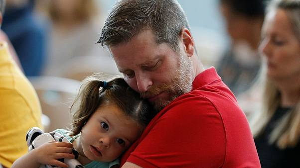 Mark Angle kétéves kislányát tartja a karjában a gyászmisén