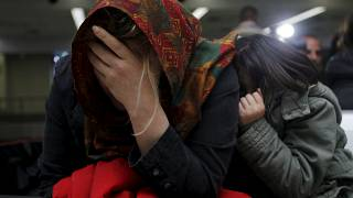 An Iraqi refugee woman returning from Finland reacts after arriving at Bagh