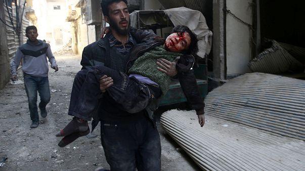 شاب يحاول إسعاف طفل أصيب في القصف على الغوطة الشرقية بدمشق