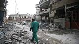 A medic walks through the rubble of a bombed clinic