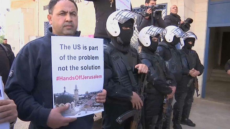 شخص يرفع لافتة للاحتجاج على زيارة وفد أمريكي للضفة الغربية