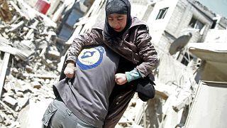 """عنصر من الدفاع المدني """"القبعات البيضاء"""" يحمل امرأة مصابة بالغوطة الشرقية"""